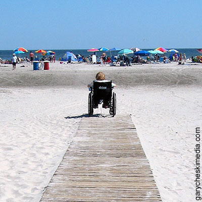 woman in wheelchair at end of path on the beach